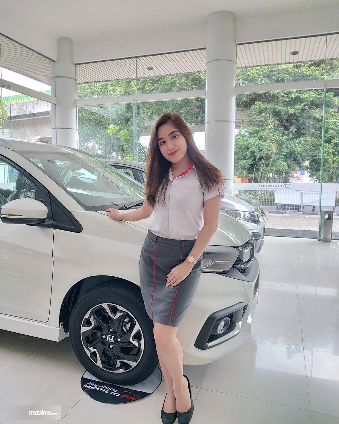 Foto menunjukkan seorang sales berpose bersama mobil Honad di Diler Honda Cempaka Putih