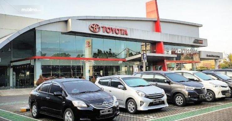 Gambar ini menunjukkan salah satu diler mobil Toyota dengan banyak mobilk diparkir di depan