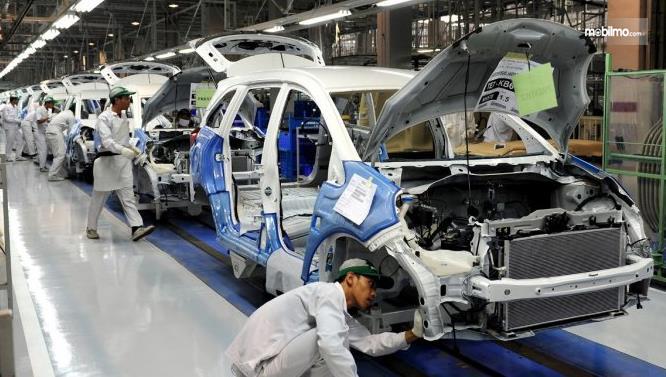 Gambar ini menunjukkan beberapa pria sedang produksi mobil
