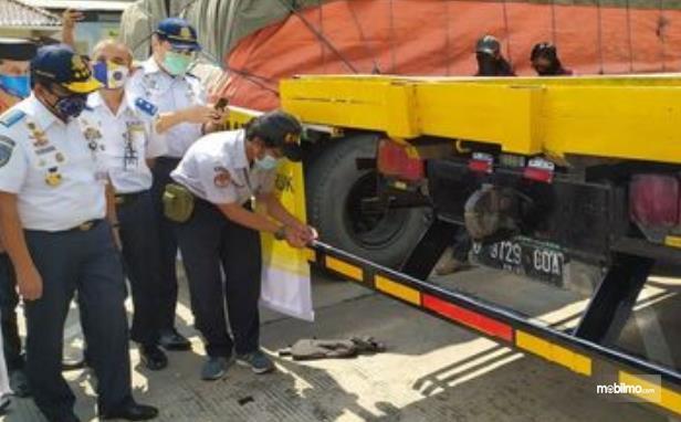 Gambar ini menunjukkan beberapa petugas Kemenhub melihat perisai kolong pada mobil truk