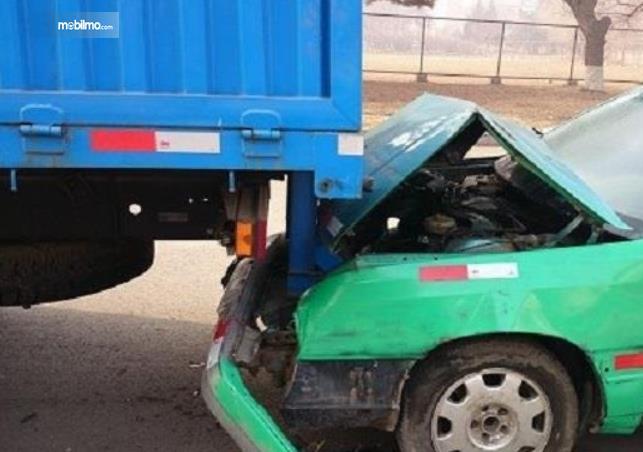 Gambar ini menunjukkan sebuah mobil kecil menabran mobil truk biru