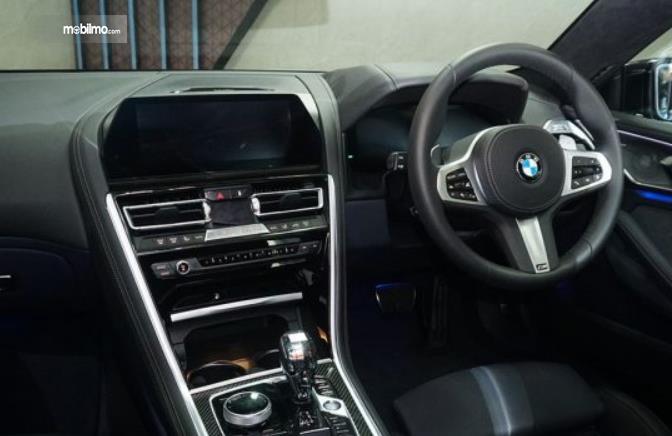 Gambar ini menunjukkan dashboard, head unit dan kemudi mobil BMW Seri 8