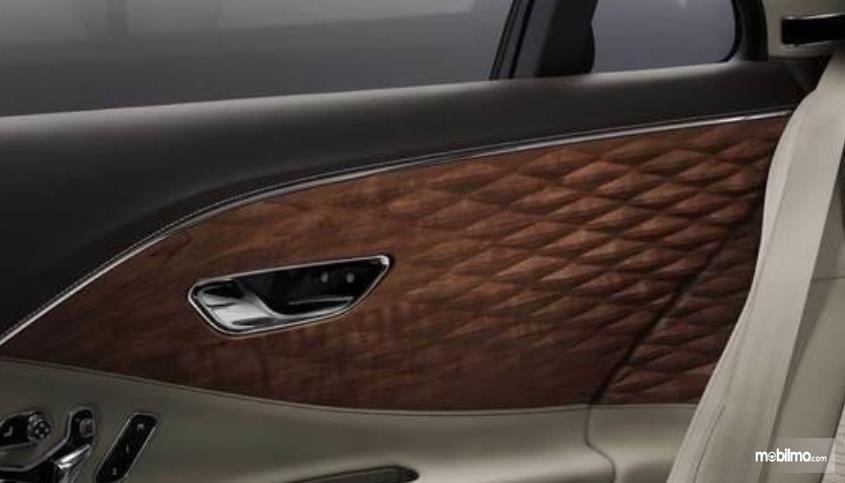 Gambar ini menunjukkan panel instrumen kayu dengan motif 3 dimensi pada pintu mobil