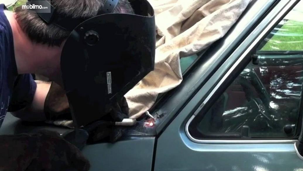 Gambar ini menunjukkan seseorang mengelas bodi mobil
