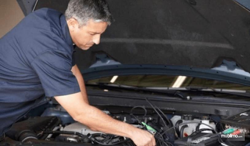 Gambar ini menunjukkan seorang pria sedang memegang mesin mobil