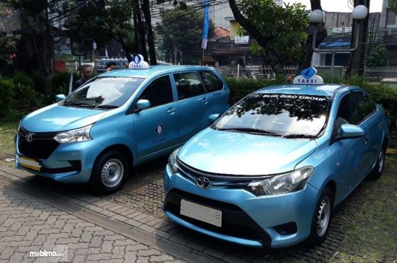 Gambar ini menunjukkan 2 buah mobil taksi dengan warna biru