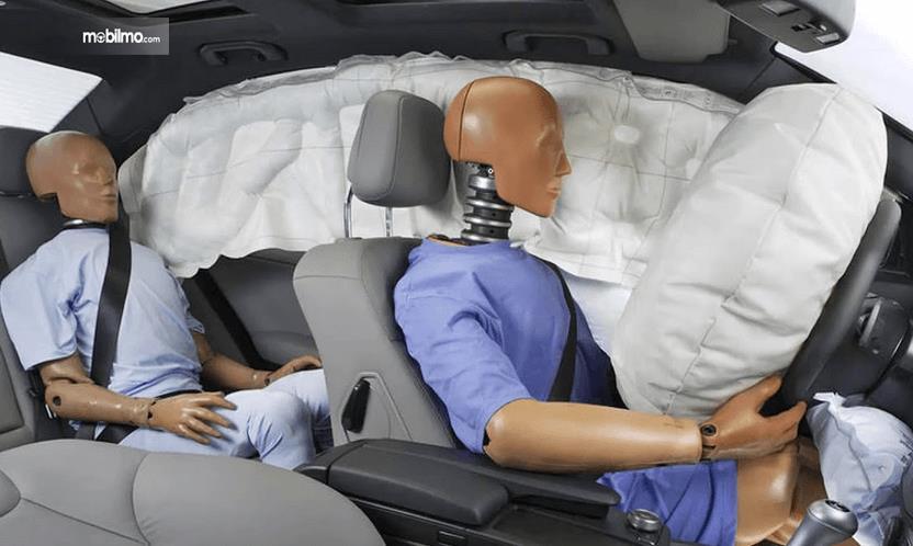 Gambar ini menunjukkan airbag yang mengembang dengan boneka orang untuk pengetesan kinerja airbag