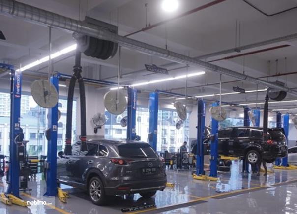 Gambar ini menunjukkan beberapa mobil Mazda sedang diservis
