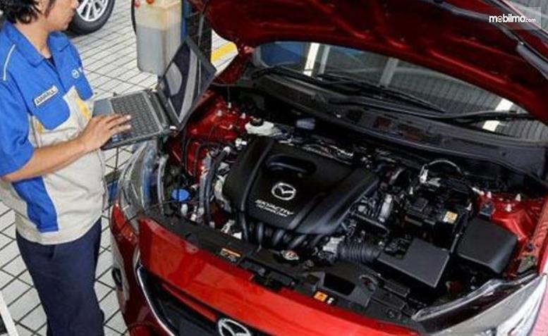 Gambar ini menunjukkan seorang mekanik sedang melihat mesin mobbil Mazda