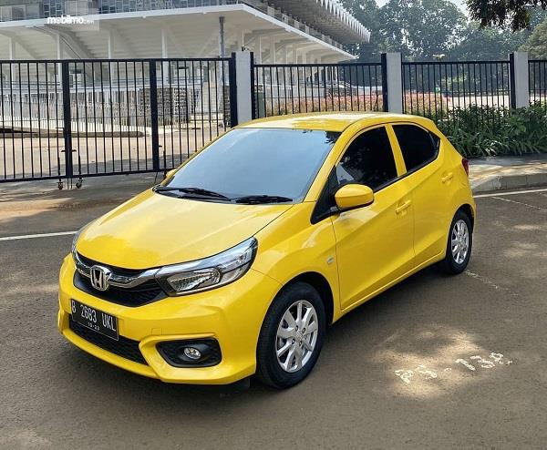 Foto menunjukkan Honda Brio warna kuning tampak dari samping depan