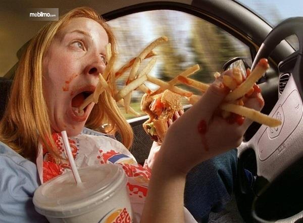 Gambar menunjukkan gambaran Bahaya makan sambil mengemudi
