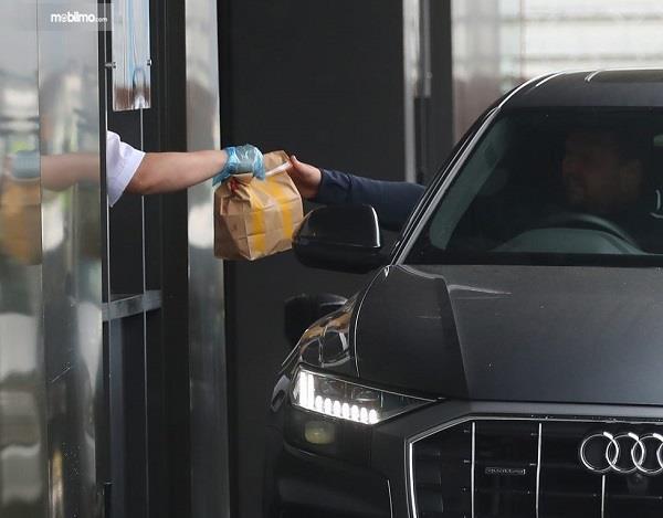 Foto menunjukkan pengendara membeli makanan drive thru