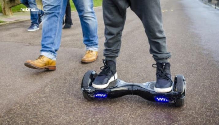 Gambar ini menunjukkan seseorang naik hoverboard