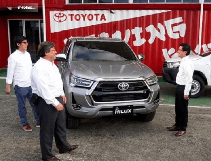 Gambar ini menunjukkan beberapa orang berdiri disamping Toyota Hilux Terbaru