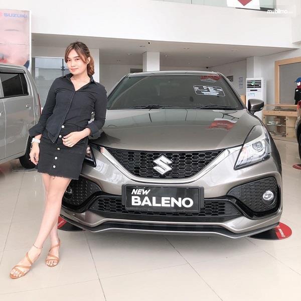Foto menunjukkan sales berpose dengan Suzuki New Baleno