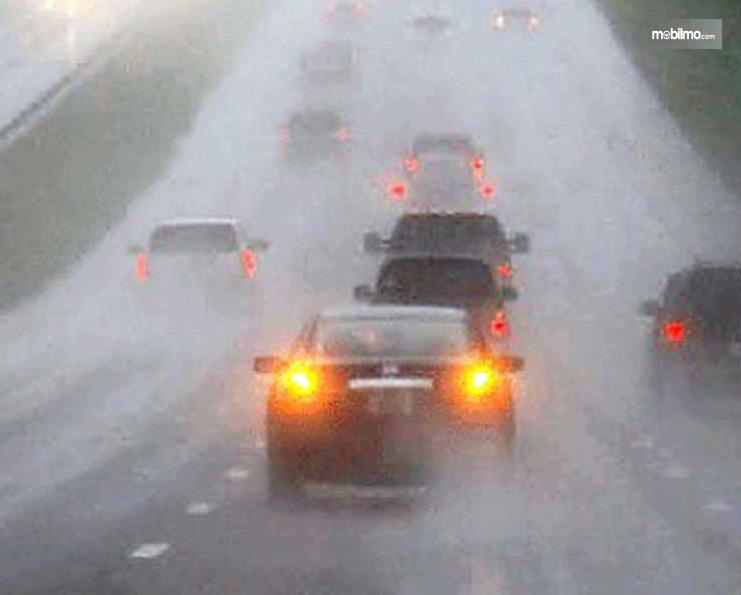 Gambar ini menunjukkan beberapa mobil dan ada yang menyalakan lampu Hazard