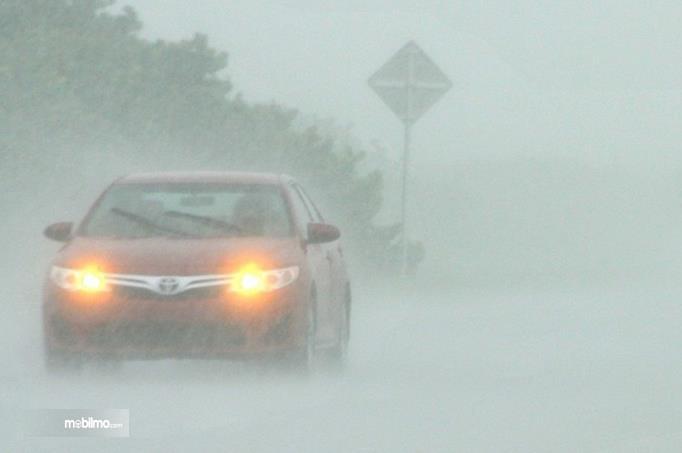 Gambar ini menunjukkan sebuah mobil menyalakan lampu dalam kondisi hujan deras