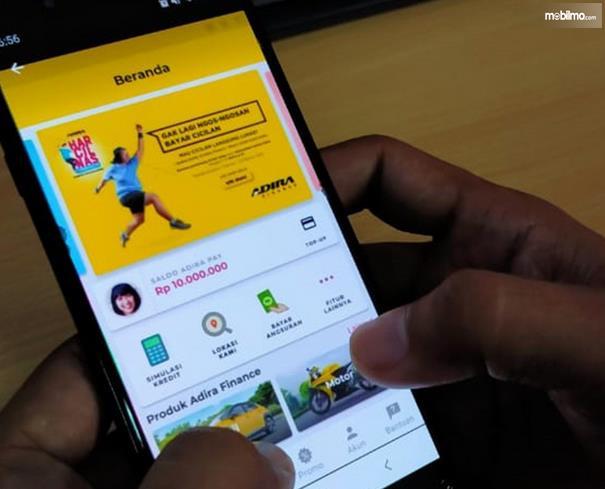 Gambatr ini menunhjukkan beberapa ibu jari menekan layar yang membuka aplikasi Adiraku