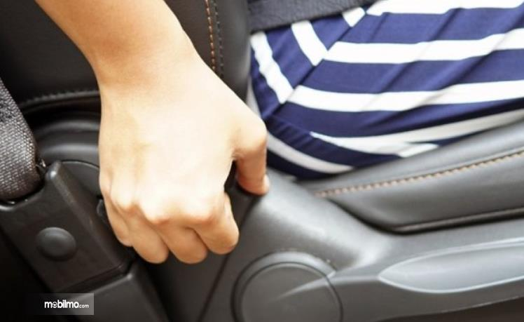 Gambar ini menunjukkan seseorang mengatur jok mobil