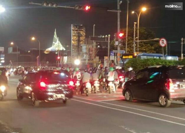 Gambar ini menunjukkan banyak sepeda motor dan 2 mobil di lampu merah