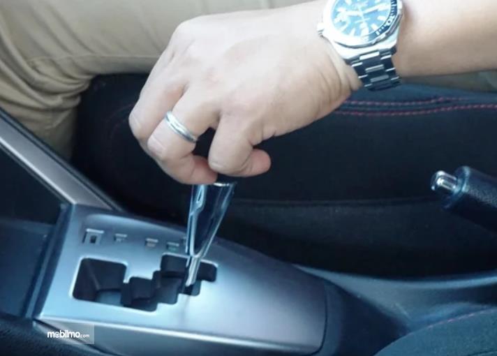 Gambar ini menunjukkan sebuah tangan memagang tuas transmisi mobil matic