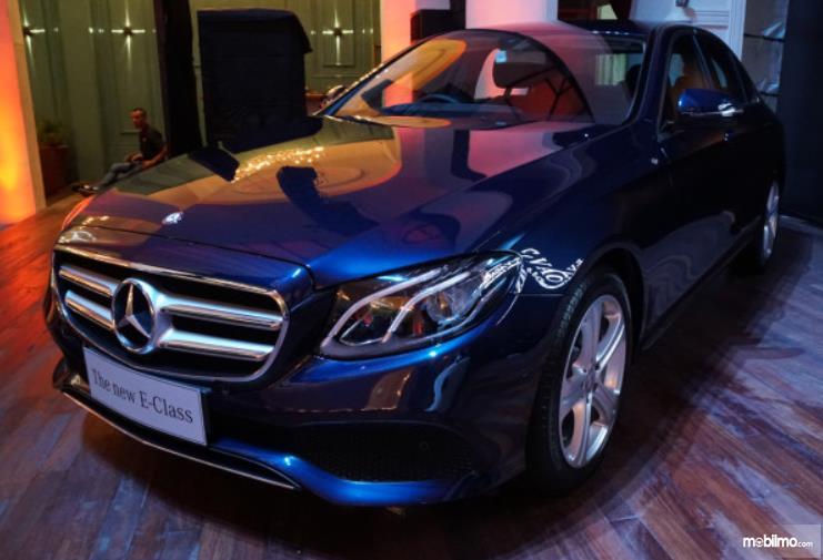 Gambar ini menunjukkan mobil Mercedes-Benz EClass warna bru tampak depan