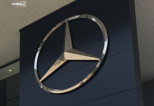Gambar ini menunjukkan logo Mercedes-Benz dengan aksen warna chrome