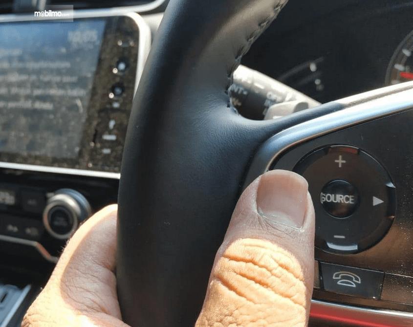 Gambar ini menunjukkan jari tangan menekan tombol di kemudi mobil