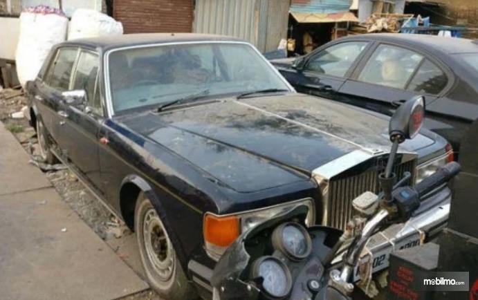 Gambar ini menunjukkan mobil Rolls-Royce Silver Spur II warna hitam dalam kondisi berdebu
