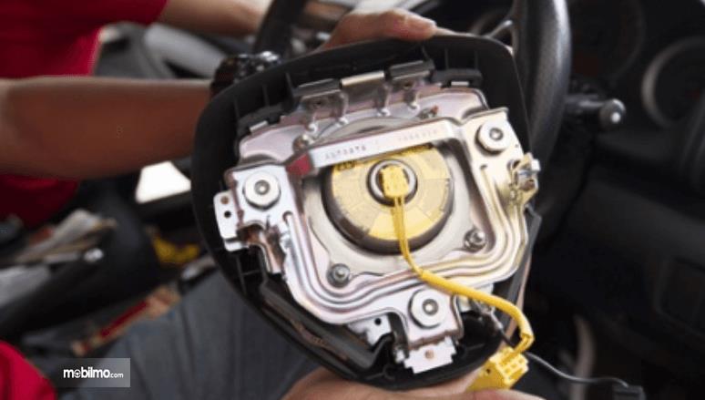 Gambar ini menunjukkan inflator airbag pada mobil