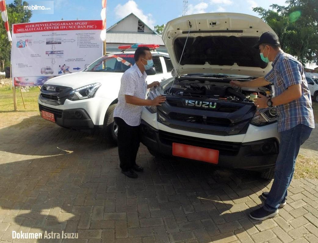 Gambar ini menunjukkan 2 orang melihat mesin mobil Isuzu Mu-X Ambulans