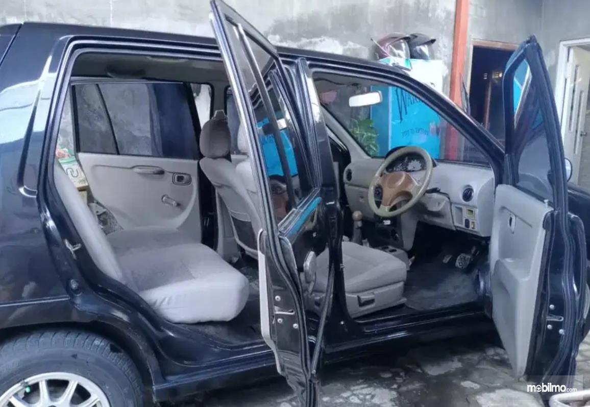 Gambar ini menunjukkan jok mobil dan pintu terbuka