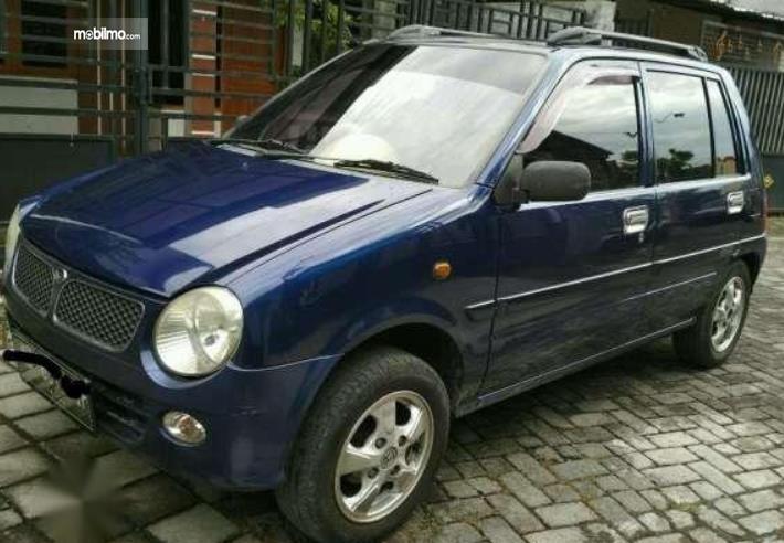 Gambar ini menunjukkan bagian samping Daihatsu Ceria 2003 warna biru