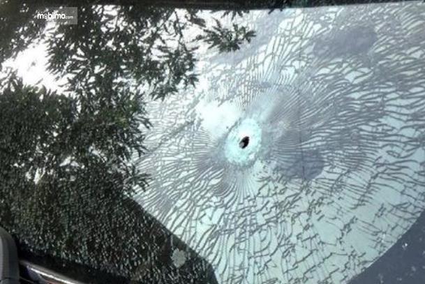 Gambar ini menunjukkan kaca mobil yang berlubang karena tertembak