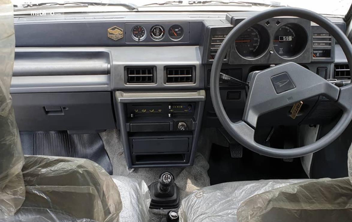 Gambar ini menunjukkan dashboard dan kemudi mobil Daihatsu Taft 1996
