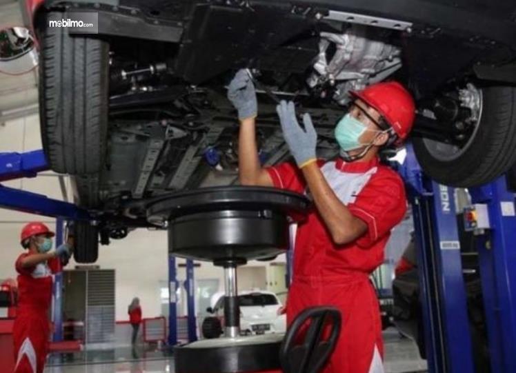 gambar ini menunjukkan seorang mekanik memeriksa mesin mobil