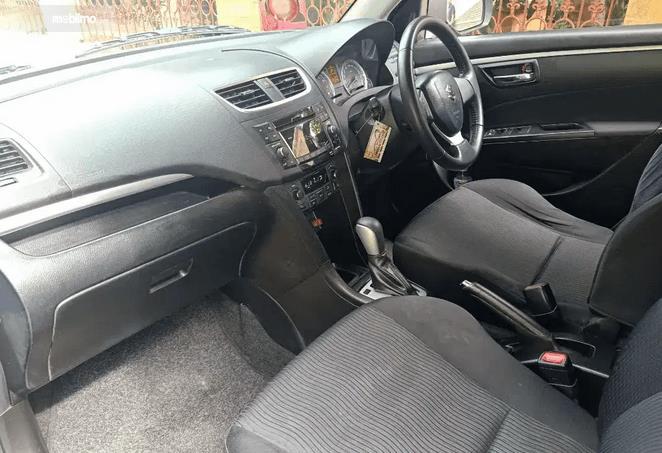 Gambar ini menunjukkan dashboard dan jok mobil Mobil Suzuki Swift 2013