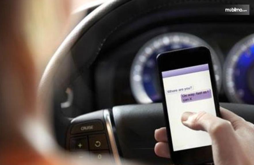 Gambar ini menunjukkan pengemudi mobil memegang ponsel