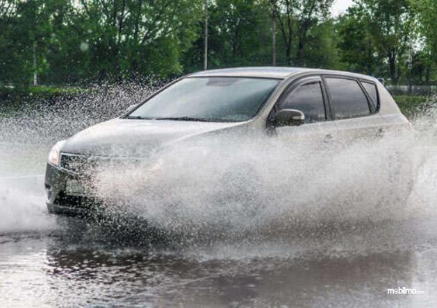 Gambar ini menunjukkan mobil yang melaju di genangan air