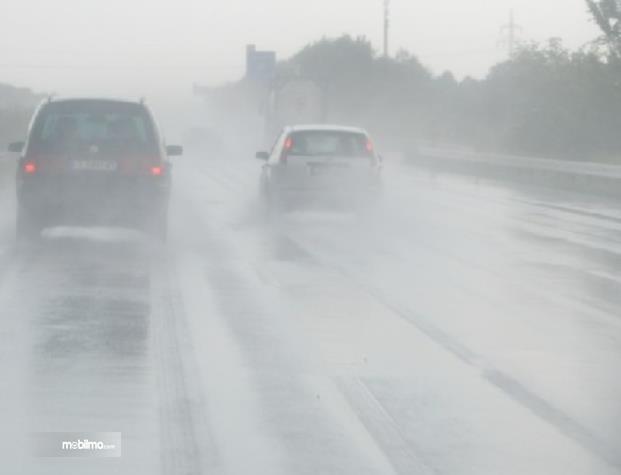 Gambar ini menunjukkan beberapa mobil melaju di jalan tol dalam  kondisi hujan
