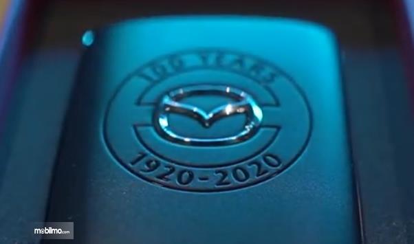 Gambar ini menunjukkan logo Mazda Edisi 100 Tahun