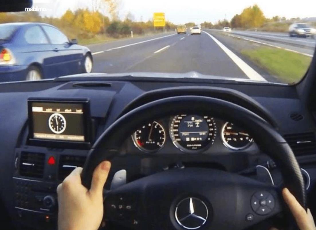 Gambar ini menunjukkan kaca mobil terlihat kendaraan lain sedang melaju