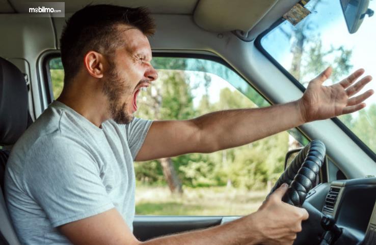 Gambar ini menunjukkan seorang pengemudi pria sedang emosi