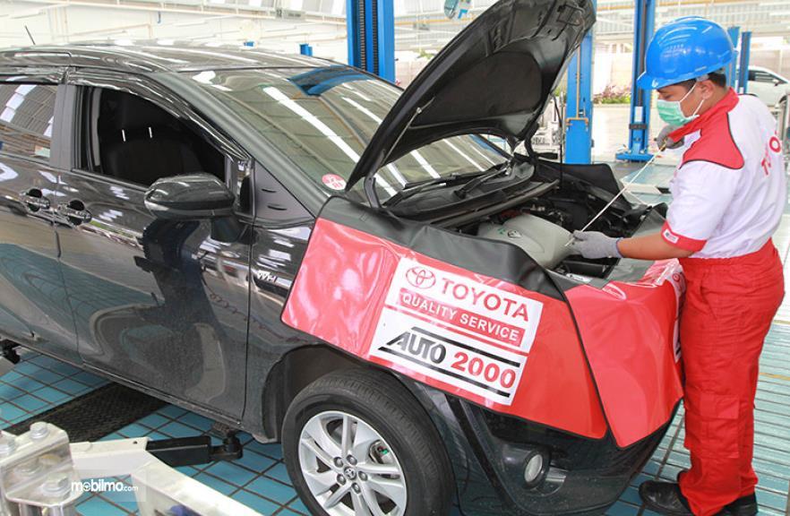 Gambar ini menunjukkan seorang mekanik sedang memeriksa mesin mobil