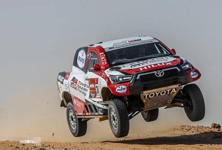 Gambar ini menunjukkan Toyota Hilux tampak berada di atas tanah seperti sedang terbang