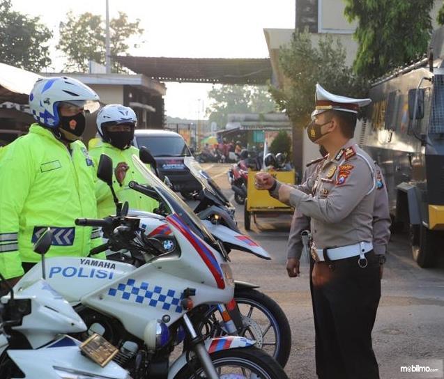 Gambar ini menunjukkan beberapa polisi sedang berbincang
