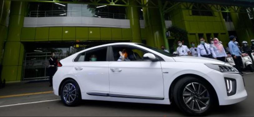 Gambar ini menunjukkan mobil listrik warna putih tampak samping