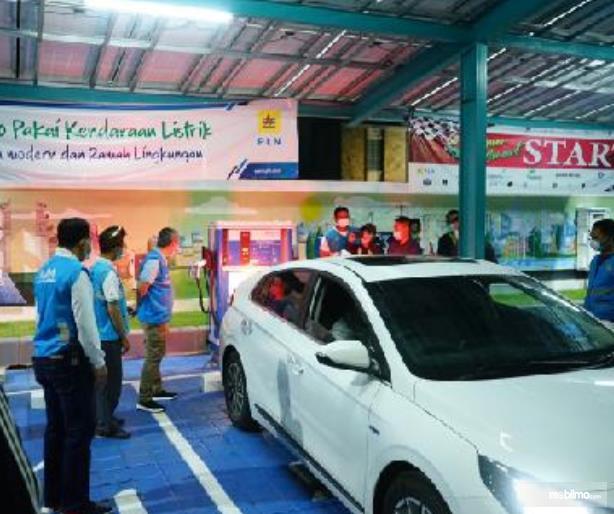Gambar ini menunjukkan satu mobil listrik dan banyak orang sedang berdiri