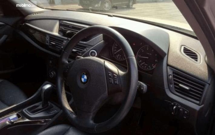 Gambar ini menunjukkan dashboard dn kemudi mobil BMW X1 sDrive18i 2011