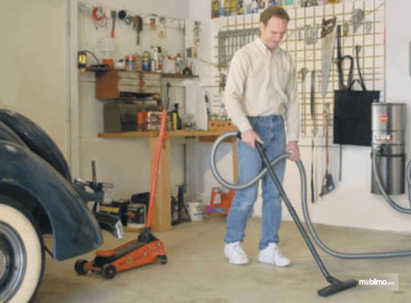 Gambar ini menunjukkan seorang pria membersihkan garasi mobil